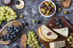 Snacks of blue cheese, olives, bread and grapes. Snacks for wine from blue cheese, olives, bread and grapes Stock Photo