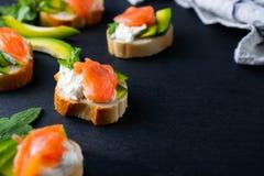 Snacks, bruschetta with cream cheese, avocado and salmon stock photography