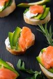 Snacks, bruschetta with cream cheese, avocado and salmon royalty free stock photo