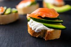 Snacks, bruschetta with cream cheese, avocado and salmon stock image