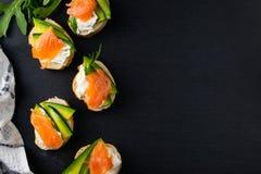 Snacks, bruschetta with cream cheese, avocado and salmon, overhead flat lay stock photo