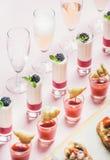 Snacks, brushetta sandwiches, gazpacho shots, desserts over pastel pink background. Close-up of various snacks, brushettas, gazpacho shots, desserts with berries stock image