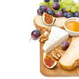 Snacks - cheese, bread, figs, grapes, honey and nuts isolated Stock Images