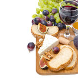 Snacks - cheese, bread, figs, grapes, nuts and a glass of wine Royalty Free Stock Image