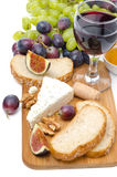 Snacks - cheese, bread, figs, grapes, nuts and red wine Stock Images