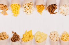 Snacks collection in craft paper cornets on white wooden board, top view, border. Snacks collection in craft paper cornets on white wooden board, top view stock images
