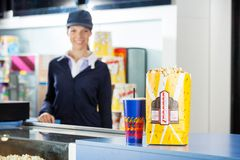 Snacks On Concession Stand At Cinema With Worker Royalty Free Stock Photography