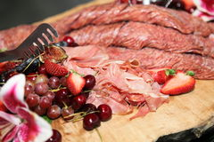 Snacks. Delicious cold cuts on a wood tray Royalty Free Stock Image