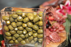 Snacks. Delicious cold cuts on a wood tray next to olives Royalty Free Stock Photo