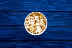 Snacks for film watching. Popcorn in paper cup on blue background top view copy space stock photo