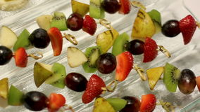 Snacks with fruit on skewers lying stock footage