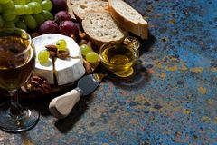 snacks, glass of wine and Camembert cheese and dark background Stock Image