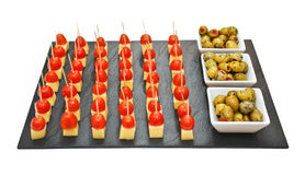 Snacks made with cheese and tomato pieces on a black tray near three bowls with green olives Stock Photos