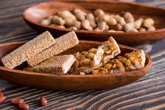 Snacks - mengeling van energiebars met pinda, sesam en zonnebloemzaden op een houten achtergrond Noten in karamel, het voedsel va royalty-vrije stock fotografie