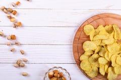 Snacks op een witte houten lijst Spaanders, pistaches, droge kaas royalty-vrije stock afbeelding