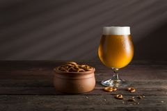 Snacks and pale beer. Glass of cold pale beer with a bowl of pretzels on a rustic wooden table Royalty Free Stock Photo