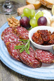 Snacks on a plate - sausage, sun-dried tomatoes, nuts, fruit. Cheese, close-up Stock Images