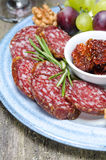 Snacks on a plate - sausage, sun-dried tomatoes, nuts, fruits Royalty Free Stock Photo
