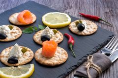 Snacks on the slate plate. Crackers with cheese and red fish. Snacks on the slate plate. Crackers with cheese and red fish Stock Images