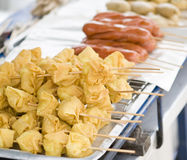 Snacks sold by street vendor in bangkok. Fried wonton and sausages on bamboo sticks sold by street vendor in bangkok, thailand Royalty Free Stock Photo
