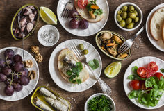 Snacks table - canned sardines, mussels, octopus, grape, olives, tomato on wooden table, top view. Stock Images
