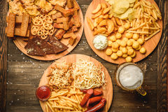 Snacks to beer on wooden background top view. A variety of snacks for beer. Cheese, sausages, chips, snacks, potatoes, rustic, sauce the beer mugs on wooden Royalty Free Stock Photos