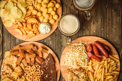 Snacks to beer on wooden background top view. A variety of snacks for beer. Cheese, sausages, chips, snacks, potatoes, rustic, sauce the beer mugs on wooden Royalty Free Stock Image