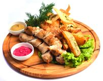 Snacks to beer on a wooden board. Bavarian fried sausages, fried potatoes, chips isolated on white background.  Royalty Free Stock Photos