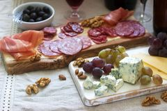 Snacks to wine from various types of sausages, ham, cheese, nuts and grapes. Rustic style. Selective focus royalty free stock images