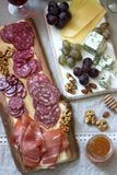 Snacks to wine from various types of sausages, ham, cheese, nuts and grapes. Rustic style. Selective focus stock photo