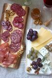 Snacks to wine from various types of sausages, ham, cheese, nuts and grapes. Rustic style. Selective focus royalty free stock photo