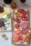 Snacks to wine from various types of sausages, ham, cheese, nuts and grapes. Rustic style. Selective focus royalty free stock image