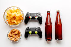 Snacks for video games on white background top view. Snacks for playing video games with joypad and beer on white desk background top view Stock Images