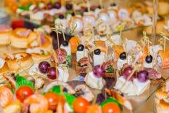 Snacks, vissen en vleesspecialiteiten op het buffet Een feestontvangst Gediende lijsten catering stock afbeelding