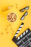 Snacks voor film het letten op Popcorn en soda dichtbij clapperboard, glazen op gele hoogste mening als achtergrond Royalty-vrije Stock Afbeeldingen