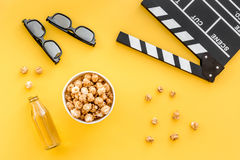 Snacks voor film het letten op Popcorn en soda dichtbij clapperboard, glazen op gele hoogste mening als achtergrond Stock Foto's