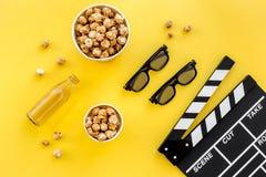 Snacks voor film het letten op Popcorn en soda dichtbij clapperboard, glazen op gele hoogste mening als achtergrond Stock Foto