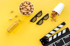 Snacks voor film het letten op Popcorn en soda dichtbij clapperboard, glazen op gele hoogste mening als achtergrond copyspace Stock Afbeelding
