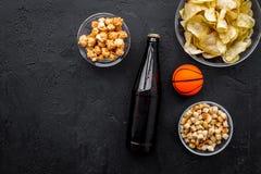 Snacks voor het letten van sport op gelijken en spelen op TV Chips, popcorn, beschuiten dichtbij drank en bal op zwarte bovenkant Royalty-vrije Stock Afbeelding