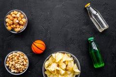 Snacks voor het letten van sport op gelijken en spelen op TV Chips, popcorn, beschuiten dichtbij drank en bal op zwarte bovenkant Stock Foto