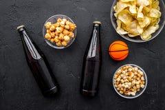 Snacks voor het letten van sport op gelijken en spelen op TV Chips, popcorn, beschuiten dichtbij drank en bal op zwarte bovenkant Stock Foto's