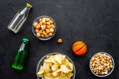 Snacks voor het letten van sport op gelijken en spelen op TV Chips, popcorn, beschuiten dichtbij drank en bal op zwarte bovenkant Stock Fotografie