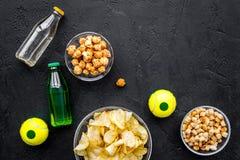 Snacks voor het letten van sport op gelijken en spelen op TV Chips, popcorn, beschuiten dichtbij drank en bal op zwarte bovenkant Royalty-vrije Stock Foto's