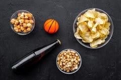 Snacks voor het letten van sport op gelijken en spelen op TV Chips, popcorn, beschuiten dichtbij drank en bal op zwarte bovenkant Royalty-vrije Stock Foto
