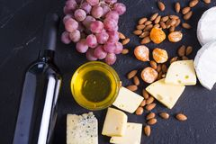 Snacks with wine - bottle, various types of cheeses, figs, nuts, honey, grapes. On a black stone background royalty free stock photography