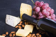 Snacks with wine - bottle, various types of cheeses, figs, nuts, honey, grapes. On a black stone background stock photos