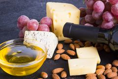 Snacks with wine - bottle, various types of cheeses, figs, nuts, honey, grapes. On a black stone background royalty free stock image