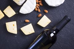 Snacks with wine - bottle, various types of cheeses, figs, nuts, honey, grapes. On a black stone background royalty free stock photos