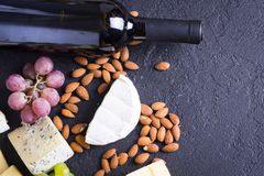 Snacks with wine - bottle, various types of cheeses, figs, nuts, honey, grapes. On a black stone background stock photo