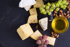 Snacks with wine - bottle, various types of cheeses, figs, nuts, honey, grapes. On a black stone background stock images